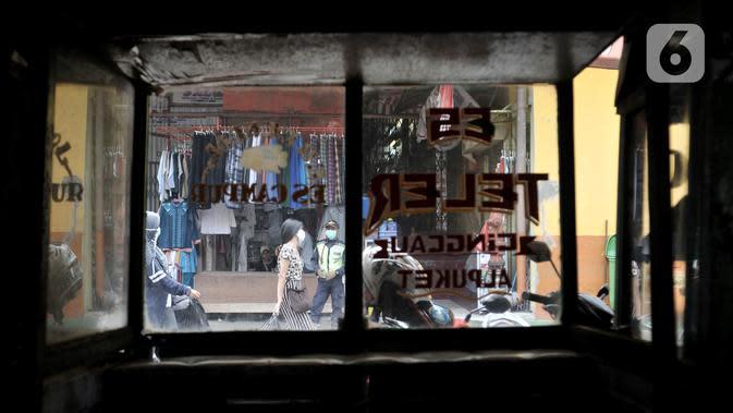 Pengujung melintas di depan kios makanan yang tutup di Pasar Jatinegara, Jakarta, Kamis (26/3/2020). Pedagang yang masih tetap membuka toko pun mengeluh karena penjualan menurun hingga 80 persen. (merdeka.com/Iqbal S. Nugroho)