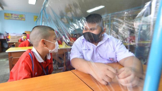 Para siswa saling mengobrol dengan dibatasi lembaran plastik di sebuah sekolah di Bangkok, Thailand (1/7/2020). Sekolah-sekolah di Thailand telah dibuka kembali pada Rabu (1/7). (Xinhua/Rachen Sageamsak)