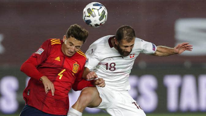 Pemain Spanyol, Pau Torres, duel udara dengan pemain Swiss, Admir Mehmedi, pada laga UEFA Nations League di Stadion Alfredo di Stefano, Minggu (11/10/2020). Spanyol menang dengan skor 1-0. (AP Photo/Manu Fernandez)