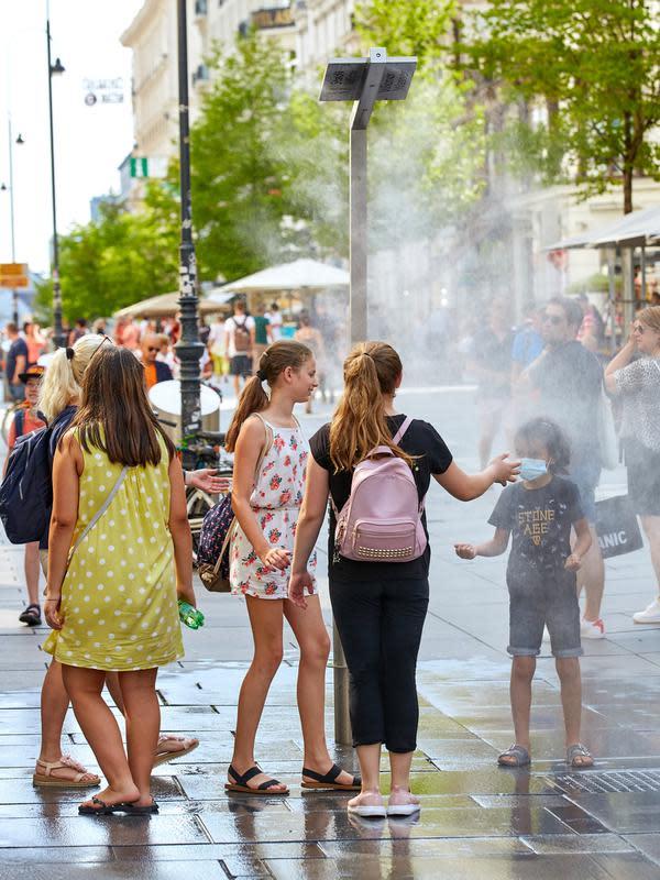 Orang-orang menyejukkan badan di bawah fasilitas penyemprot air bertenaga surya, Wina, Austria, 7 Agustus 2020. Wina menarik perhatian dunia dengan model pembangunan kota hijaunya yang menyokong perjalanan ramah lingkungan, penghijauan perkotaan, dan gaya hidup hijau. (Xinhua/Georges Schneider)