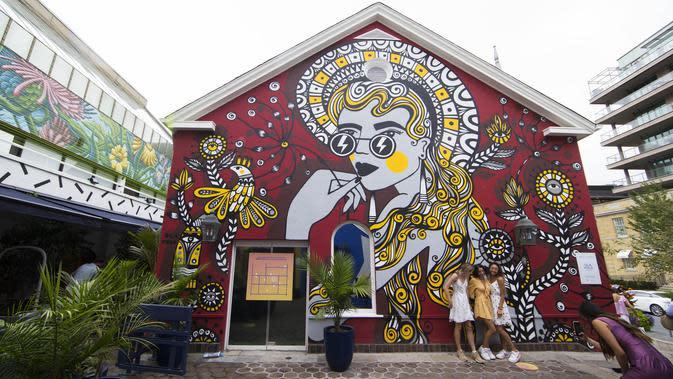 Sejumlah orang berfoto di depan mural dalam acara Yorkville Murals 2020 di Toronto (29/8/2020). Dengan karya mural artistik dan implementasi aktivasi budaya, acara tahunan ini dimulai Jumat (28/8) hingga Minggu (30/8) sebagai perayaan seni publik dan gerakan mural kontemporer. (Xinhua/Zou Zheng)
