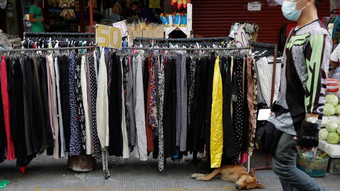 Seekor anjing tidur di bawah toko darurat untuk pakaian bekas, setelah pelonggaran lockdown, di pusat kota Manila, Filipina, Rabu (2/9/2020). Pemerintah melonggarkan lockdown meskipun negara tersebut memiliki infeksi virus corona terbanyak di Asia Tenggara. (AP Photo/Aaron Favila)