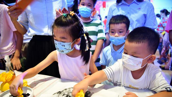 Anak-anak menjajal membuat sablon (rubbing) dalam acara perayaan Festival Pertengahan Musim Gugur di Museum Hainan, Haikou, ibu kota Provinsi Hainan, China selatan (1/10/2020). (Xinhua/Guo Cheng)