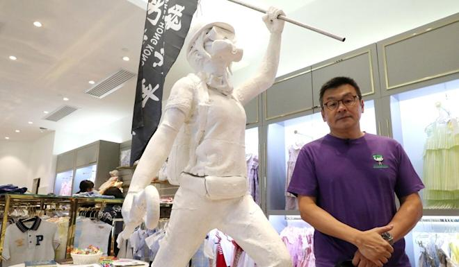 Herbert Chow, CEO of Chickeeduck Group, poses next to the statue that put his clothing chain at the centre of a political controversy in recent weeks. Photo: Edmond So