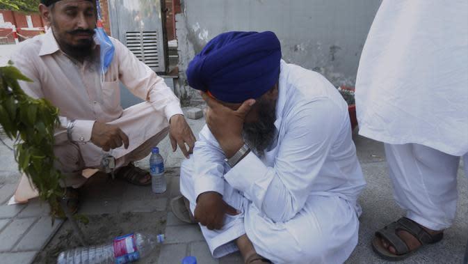 Seorang pria berduka atas kematian anggota keluarganya dalam kecelakaan bus dan kereta api di Sheikhupura, Pakistan, Jumat (3/7/2020). Kecelakaan sering terjadi di perlintasan kereta api tak berawak di Pakistan, yang sering kali tak memiliki penghalang dan terkadang sinyal. (AP Photo/K.M. Chaudary)