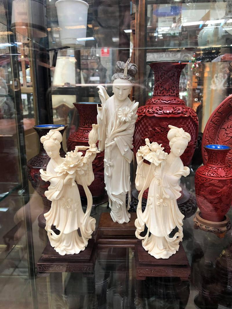 Three ivory statues are in a glass cabinet in an antiques shop.
