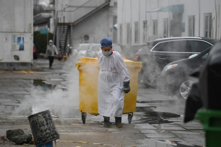 A worker carts a bin loaded with medical waste to a storage facility at the Youan Hospital in Beijing, which is treating coronavirus patients