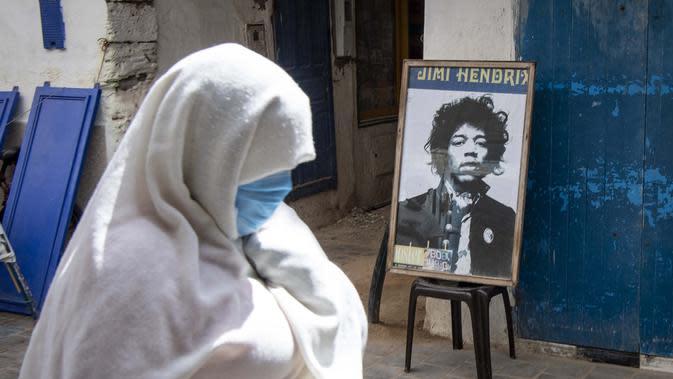 Warga melintas di depan poster Jimi Hendrix kota pesisir Maroko Essaouira pada 10 September 2020. Kisah tentang petualangan Hendrix di Maroko ada beragam versi; dia melintasi negara dengan van, mencoba membeli sebuah pulau di lepas pantai Essaouira dan seluruh desa Diabat. (AFP/Fadel Senna)