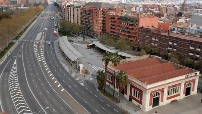 Sebuah jalan terlihat kosong di Barcelona, Spanyol, Minggu (15/3/2020). Pemerintah Spanyol memberlakukan lockdown selama 15 hari ke depan untuk menghambat penyebaran virus corona COVID-19. (AP Photo/Joan Mateu)