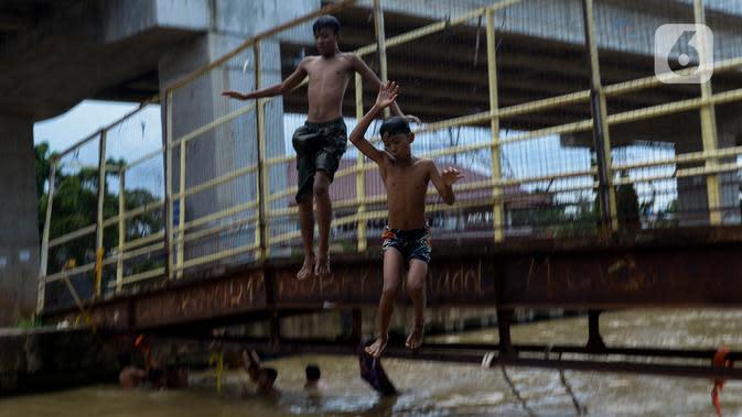 Anak-anak bermain dan berenang di aliran Kalimalang, Jakarta, Sabtu (15/2/2020). Cuaca yang tidak menentu membuat aliran air terkadang menjadi deras sehingga akan membahayakan keselamatan anak-anak saat bermain dan berenang. (merdeka.com/Imam Buhori)