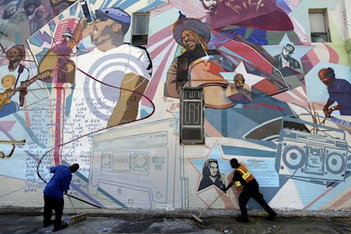 "Workmen sweep in front of a new mural honoring The Roots, Friday, May 31, 2013, in Philadelphia. As a teen growing up in Philadelphia, Tariq ""Black Thought"" Trotter got busted for graffiti and was ordered by a judge to clean up such vandalism by painting murals. Now, Trotter and his Grammy-winning band The Roots are scheduled to attend Friday the unveiling of a city-sanctioned mural in their honor. (AP Photo/Matt Rourke)"