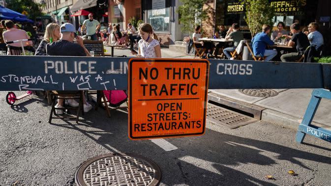 Pengunjung duduk di luar restoran yang mengoperasikan area luar ruangan (outdoor) hingga ke trotoar dan jalanan di New York pada 3 Oktober 2020. Kota tersebut mengizinkan restoran membuat area makan outdoor sebagai upaya mengatasi dampak ekonomi COVID-19 yang berkelanjutan. (AP Photo/John Minchillo)