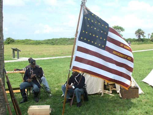 "Re-enactors sit in an encampment at Fort Moultrie on Sullivans Island, S.C., on Thursday, July 18, 2013. The re-enactors gathered to commemorate the 150th anniversary of the famed Civil War attack by the 54th Massachusetts Volunteer Infantry in a fight commemorated in the film ""Glory."" Prayers, a wreath-laying, candlelight and period music are planned to observe the attack on Battery Wagner that debunked the myth that black soldiers could not fight. (AP Photo/Bruce Smith)"