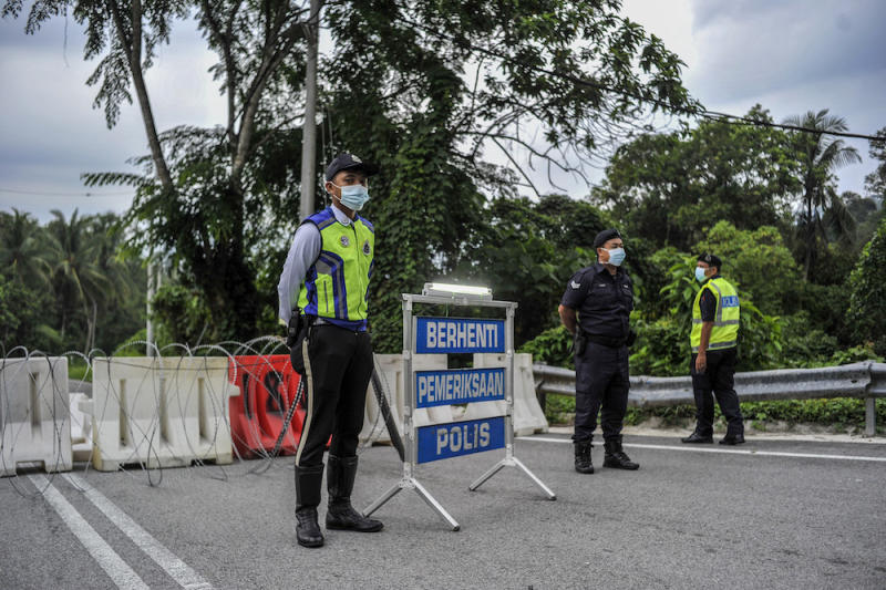 Police officers conducting checks at a roadblock during the enhanced movement control order (EMCO) in seven villages in Hulu Langat, March 30, 2020. — Picture by Shafwan Zaidon