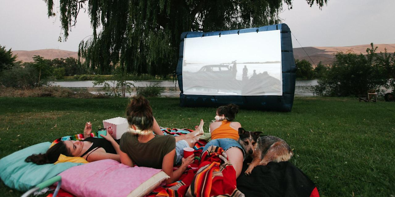 "<p>Whether it's a block party or an intimate date night, there's just something dreamy about watching a movie under the stars. Yes, <a href=""https://variety.com/2020/film/news/movie-theaters-reopening-california-1234631985/"" target=""_blank"">movie theaters are slowly opening up again,</a> but the thrill of an outdoor movie in your backyard or on your roof won't fade. It takes a little preparation and some purchasing power to <a href=""https://www.howtogeek.com/227672/the-htg-guide-to-throwing-a-backyard-movie-night/"" target=""_blank"">lay the foundation for your first screening</a>, as you'll need a projector with enough power to shine through the light pollution in your area and a surface to project the movie onto. Depending on your projector's capabilities, you may want to boost the volume with speakers, too.</p><p>While you <em>could</em> project onto a flat wall, fence, or bed sheet, you'll get the best picture quality with a screen. First, assess your space's access to a power source to decide if you want an inflatable or pulldown screen. Then figure out what surface you'll be sitting on, so you know how the screen can be stabilized. An inflatable screen, for example, will need a power source for its fan, and grass or dirt for the stakes that support it. </p><p>Once you have the tech angles figured out, add in layers of comfort so that you and your guests can sit through a 2-hour movie without aching backs or bug attacks. Consider who is in your audience when you're deciding on seating. Adults will want supportive beach chairs or outdoor loungers, while kids can be comfy on the ground with blankets and pillows. <a href=""https://www.bestproducts.com/home/outdoor/g1459/citronella-candles-to-keep-mosquitos-away/"" target=""_blank"">Keep the citronella burning</a> to ward off mosquitoes, and turn on a few <a href=""https://www.bestproducts.com/appliances/small/g1068/outdoor-solar-lights/"" target=""_blank"">outdoor lights</a> so guests can get up and move about safely. Of course, no movie theater is complete without a concession stand. Load up on popcorn and snacks, and keep your drinks close and cold with a stocked cooler and insulated cups. </p><p>From the readymade <a href=""https://www.popularmechanics.com/home/how-to-plans/a32382000/build-a-backyard-movie-screen/"" target=""_blank"">to the DIY</a>, you've got options in how to have an outdoor movie night at home. We've picked our favorite items to make it easy to start your screening under the stars. </p>"