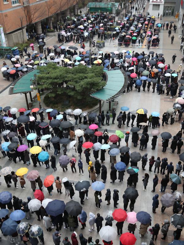 Orang-orang mengantre untuk membeli masker pelindung dari sebuah department store di Seoul, Jumat (28/2/2020). Presiden Moon Jae-in sejak akhir pekan lalu menyatakan Korea Selatan siaga satu corona dan meminta semua warga menghindari acara yang dihadiri banyak orang. (YONHAP/AFP)