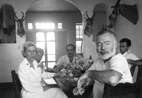"FILE - In this black and white file photo from the mid-1900's, released by the John F. Kennedy Presidential Library and Museum in Boston, shows Ernest Hemingway, second from right, and Gianfranco Ivancich, right, dining with an unidentified woman, left, wife Mary Hemingway, second from left, and Juan ""Sinsky"" Dunabeitia, center, at Hemingway's villa Finca Vigia in San Francisco de Paula, Cuba. Cuba and a private U.S. foundation are working together to preserve more of the novelist's papers and belongings that have been kept at his home near Havana since he died in 1961. The digitization of 2,000 Hemingway papers and materials will be transferred to Boston's John F. Kennedy Library. (AP Photo/John F. Kennedy Presidential Library and Museum, File)"