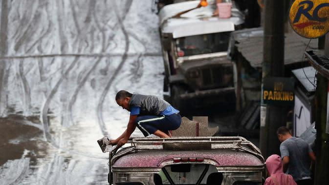 Warga membersihkan abu vulkanik dari kendaraan mereka setelah erupsi Gunung Taal di Tagaytay, Provinsi Cavite, Filipina, Senin (13/1/2020). Gunung yang terakhir meletus pada tahun 1977 tersebut melontarkan abu vulkanik mencapai 50.000 kaki (15.000 meter) ke atmosfer. (AP Photo/Aaron Favila)