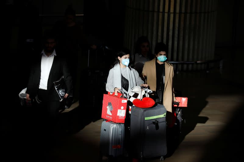 Travellers pull their suitcases while wearing masks in a terminal at Ben Gurion International airport in Lod, near Tel Aviv, Israel