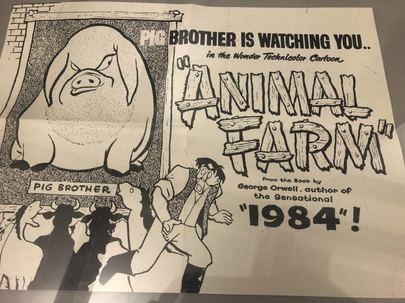 """In this Oct. 21, 2019, photo, a poster promoting a cartoon version George Orwell's novel """"Animal Farm"""" is shown at an exhibit in Albuquerque, N.M. celebrating the author's legacy. The exhibit at the University of New Mexico is tackling the themes of the novelist's work from """"1984"""" to """"Animal Farm."""" """"George Orwell: His Enduring Legacy,"""" which runs to April 2020, features posters and material related to work challenging totalitarianism. (AP Photo/ Russell Contreras)"""
