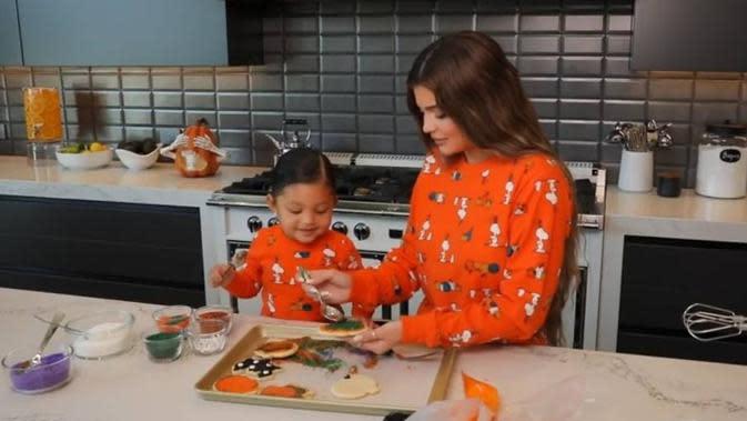 Kylie Jenner dan Stormi Webster saat menghias kue kering Halloween (dok. YouTube Kylie Jenner/ https://www.youtube.com/watch?v=tmJe-ty_jpk/ Brigitta Bellion)