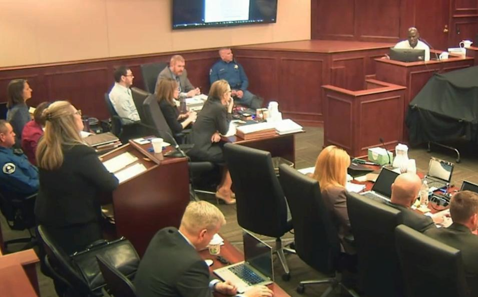 FILE - In this April 27, 2015 file image taken from Colorado Judicial Department video, Colorado theater shooter James Holmes, left rear in light-colored shirt, watches during testimony by witness Derick Spruel, upper right, on the second day of his trial in Centennial, Colo. During the first two weeks of Holmes' trial so far, jurors have asked more than 100 questions of witnesses, through notes passed to the judge. While absorbing much testimony describing the mayhem in the movie theater on the night of the killings, jurors are also grappling with the central question of the case: Was Holmes legally insane when he began shooting? (Colorado Judicial Department via AP, Pool, File)