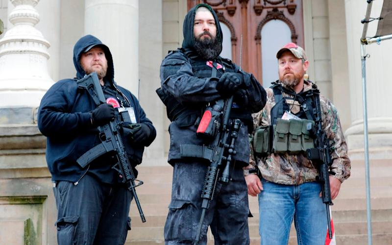 """In this file photo taken on April 30, 2020, armed protesters provide security as demonstrators take part in an """"American Patriot Rally,"""" organized by Michigan United for Liberty on the steps of the Michigan State Capitol in Lansing, demanding the reopening of businesses. - A far-right movement whose followers have appeared heavily armed at recent US protests has suddenly become one of the biggest worries of law enforcement, after one killed two California police officers. - Jeff Kowalsky/AFP"""