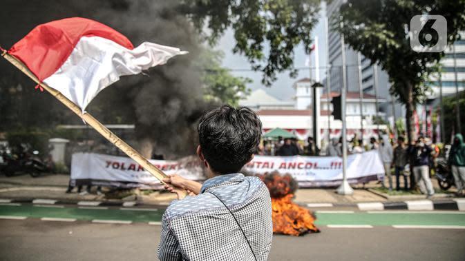 Aksi Bakar Tolak Reklamasi Pantai Ancol: Pengunjuk rasa mengibarkan bendera merah putih didepan Balaikota, Jakarta, Rabu (8/7/2020). Mereka meminta Gubernur DKI Jakarta Anies Baswedan untuk menghentikan Reklamasi Pantai Ancol. (Liputan6.com/Faizal Fanani)