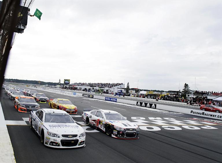 Dale Earnhardt Jr. (88) races across the line with Kevin Harvick (4) on a late race restart during the NASCAR Sprint Cup Series auto race at Pocono Raceway, Sunday, Aug. 3, 2014, Long Pond, Pa. Earnhardt won the race. (AP Photo/Mel Evans)