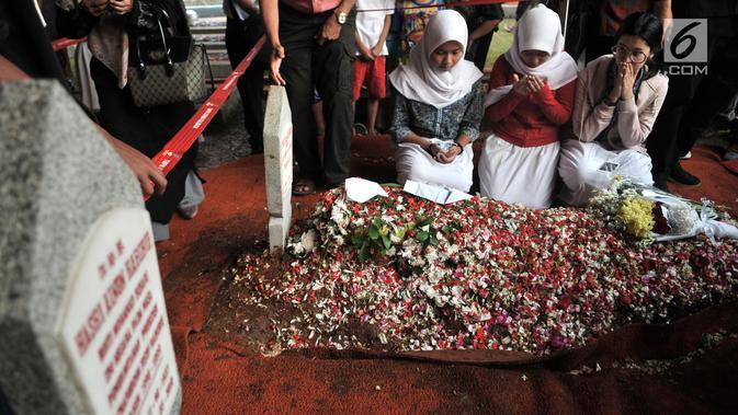 Sejumlah pelajar membaca doa di depan makam Presiden ketiga RI BJ Habibie di TMP Kalibata, Jakarta, Kamis (12/9/2019). Tidak hanya dihadiri tokoh penting, ratusan warga juga antusias datang ke TMP Kalibata untuk mengantarkan BJ Habibie ke tempat peristirahatan terakhirnya (merdeka.com/Iqbal Nugroho)
