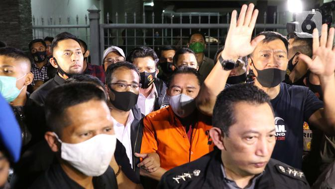 Terpidana pengalihan hak tagih atau cessie Bank Bali, Djoko Sugiarto Tjandra (rompi oranye) dikawal petugas usai tiba di Bandara Halim Perdanakusuma Jakarta, Kamis (30/7/2020). Djoko Tjandra tiba sekitar pukul 22.30 WIB dan langsung dibawa ke Bareskrim Mabes Polri. (Liputan6.com/Helmi Fithriansyah)
