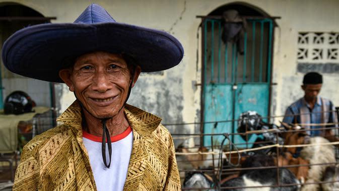 Seorang pria tersenyum di pasar yang menjual ternak menjelang perayaan Idul Fitri yang menandai akhir bulan suci Ramadan di Sibreh, provinsi Aceh (20/5/2020). (AFP/Chaideer Mahyuddin)