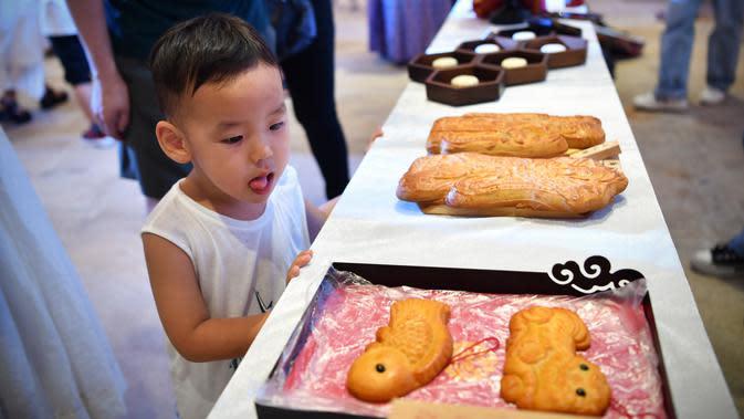 Seorang anak melihat pameran kue bulan dalam acara perayaan Festival Pertengahan Musim Gugur di Museum Hainan, Haikou, ibu kota Provinsi Hainan, China selatan (1/10/2020). (Xinhua/Guo Cheng)