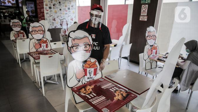Pelayan merapikan banner bergambar karakter di KFC Salemba, Jakarta, Selasa (23/6/2020). Banner bergambar tersebut berguna untuk pembatas bagi pengunjung yang makan di tempat saat fase kenormalan baru. (Liputan6.com/Faizal Fanani)