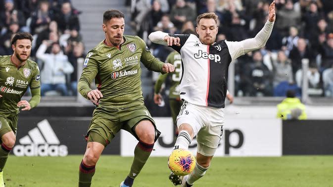 Gelandang Juventus, Aaron Ramsey berebut bola dengan pemain Cagliari, Fabrizio Cacciatore pada pertandingan lanjutan Liga Serie A Italia di Stadion Allianz, Turin (6/1/2020). Juventus menang telak atas Cagliari 4-0. (Marco Alpozzi / LaPresse via AP)