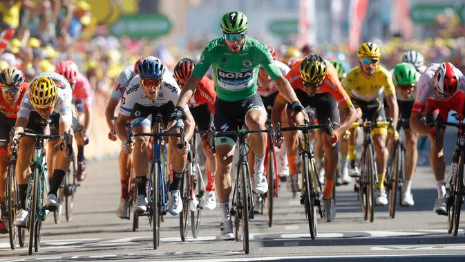 Pebalap sepeda Slovakia Peter Sagan (tengah) melakukan selebrasi saat melintasi garis finish pada etape kelima Tour de France di Colmar, Prancis, Rabu (10/7/2019). Peter Sagan menjuarai etape kelima Tour de France setelah melewati rute sepanjang 175,5 Km dari Saint-Dié-des-Vosges ke Colmar. (AP Pho