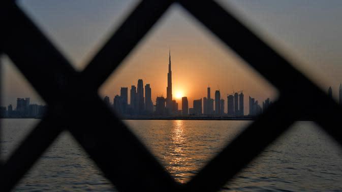 Pemandangan matahari terbenam di belakang Burj Khalifa dan gedung-gedung bertingkat lainnya, di Dubai, Uni Emirat Arab pada Sabtu (12/9/2020). (Photo by Karim SAHIB / AFP)