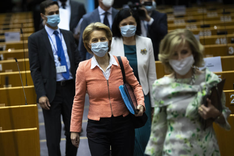 European Commission President Ursula von der Leyen, centre, wearing a face mask to protect against the spread of coronavirus, arrives to the main chamber before a plenary session at the European Parliament in Brussels, Wednesday, June 17, 2020. (AP Photo/Francisco Seco)