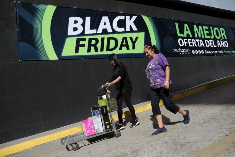 People leave a shop with purchases during the Black Friday sales in Caracas