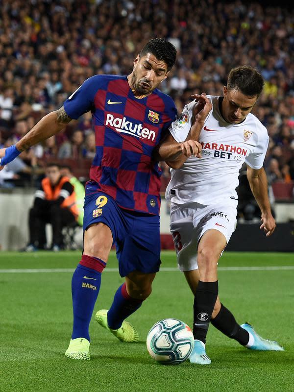 Penyerang Barcelona, Luis Suarez berebut bola dengan bek Sevilla Sergio Reguilon dalam pertandingan pekan kedelapan kompetisi La Liga Spanyol 2019-2020 di Camp Nou, Minggu (6/10/2019). Barcelona berhasil menang telak atas Sevilla dengan skor 4-0. (Josep LAGO / AFP)