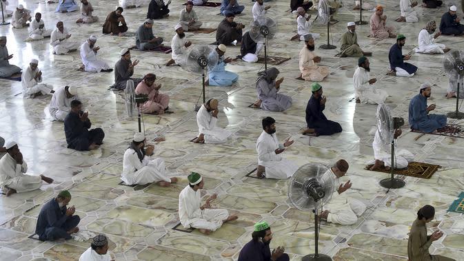 Umat muslim menerapkan jaga jarak aman atau physical distancing saat melaksanakan salat Jumat berjemaah selama Ramadan di Masjid Data Darbar, Lahore, Pakistan, Jumat (1/5/2020). Umat muslim dunia melewati Ramadan tahun ini di tengah pandemi COVID-19. (ARIF ALI/AFP)