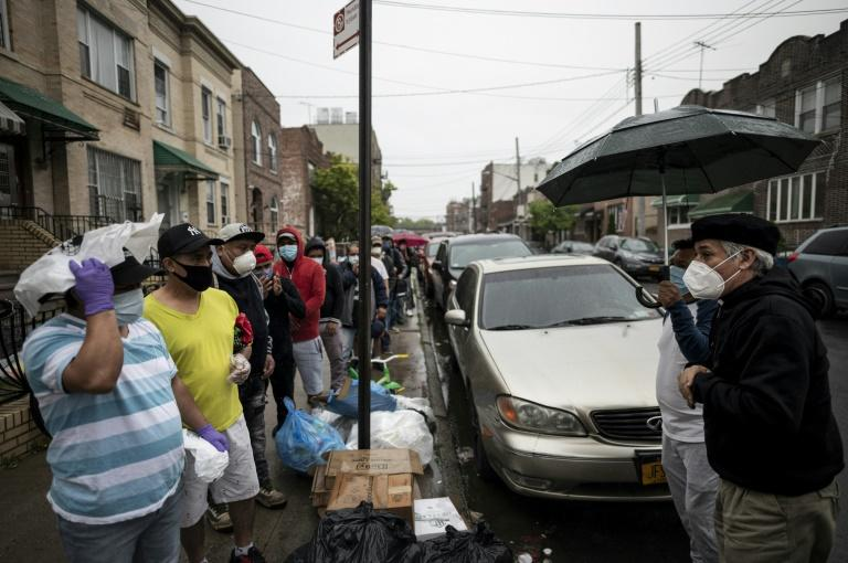 New York pastor Fabian Arias (R) talks to Guatemalans who are using his free food distribution service for immigrant communities devastated by COVID-19 in Harlem