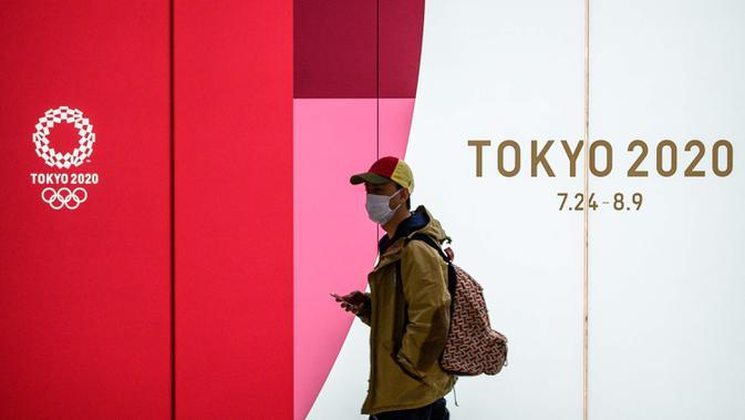 Seorang pria mengenakan masker pelindung berjalan di terowongan sebuah stasiun metro di Tokyo, Jepang, 11 Maret 2020. Pandemi virus corona COVID-19 membuat Jepang dilema untuk tetap menggelar Olimpiade 2020. (Photo by Philip FONG/AFP)