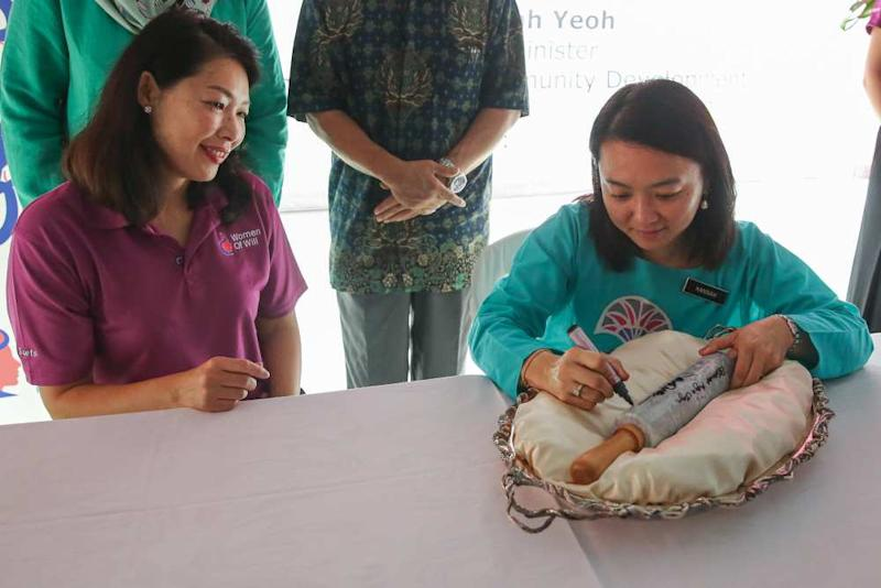 Hannah Yeoh writes on a rolling pin during the launch of the Women of Will's Community Kitchen in Kuala Lumpur May 25, 2019.
