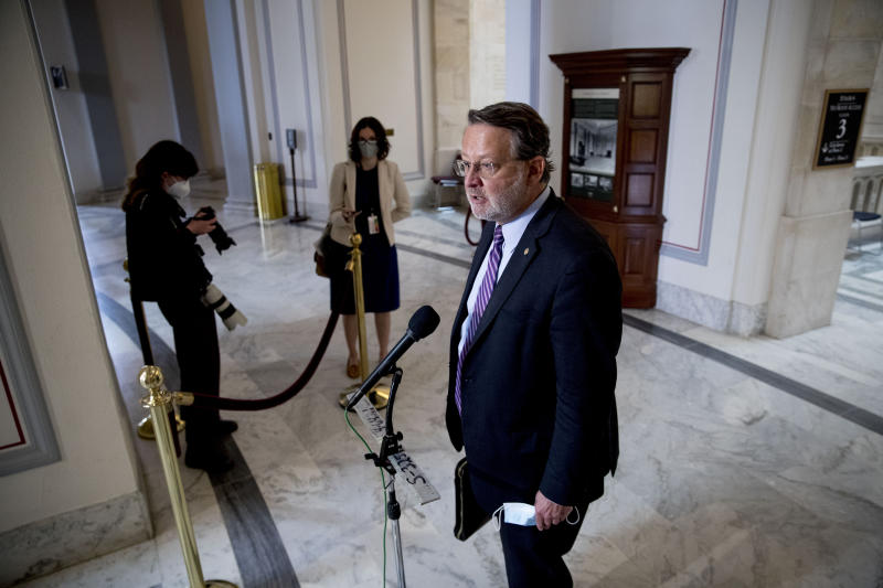 Ranking Member Gary Peters., D-Mich., speaks to a reporter at the conclusion of a Senate Homeland Security and Governmental Affairs committee meeting on Capitol Hill in Washington, Wednesday, May 20, 2020, to vote to issue a subpoena to Blue Star Strategies. (AP Photo/Andrew Harnik)