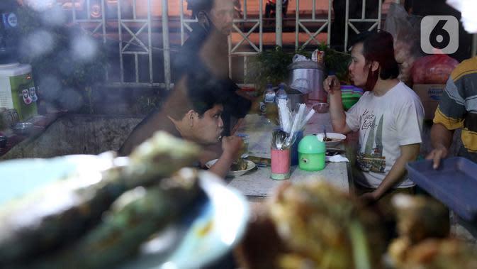 Warga berbuka puasa di kawasan Bendungan Hilir, Jakarta, Sabtu (25/4/2020). Meski ditengah pandemi virus Covid-19, masyarakat masih antusias berburu penganan berbuka puasa dengan tetap menerapkan pola jaga jarak dan memakai masker. (Liputan6.com/Helmi Fithriansyah)