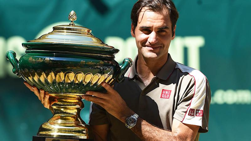 Roger Federer poses with the trophy. (Photo by CARMEN JASPERSEN/AFP/Getty Images)