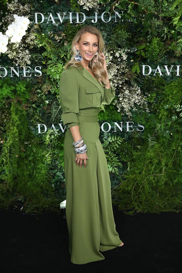 <p>Anna Heinrich matched the media wall to perfection in this striking green trouser suit. Photo: Getty Images </p>