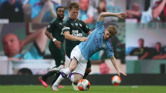 Gelandang Manchester City, Tommy Doyle (kanan) berebut bola dengan pemain tengah Newcastle United, Matt Ritchie pada lanjutan pertandingan Liga Inggris di Etihad Stadium, Kamis (9/7/2020) dini hari WIB. Manchester City menang telak 5-0 atas tamunya Newcastle United. (LEE SMITH / POOL / AFP)