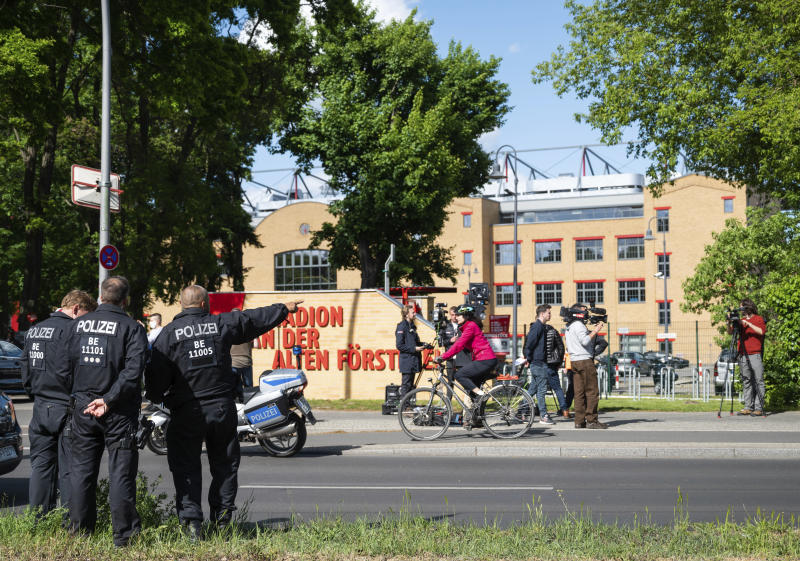 Policemen are standing outside the stadium at the old forest ranger station in Berlin, Germany, Sunday, May 17, 2020, ahead of the German Bundesliga soccer match between Union Berlin and Bayern Munich. (Christophe Gateau/dpa via AP)